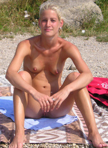Cool nudist chick in black sunglasses reading a book on the beach