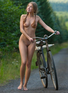 Sexy nudist girl with a bicycle