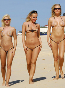 Four sexy beach chicks wearing black micro bikinis on the beach