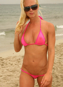Blonde hottie Jenna wears pink string micro bikini on the beach and nearby
