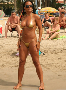 Busty brunette Georgina on the beach in golden bikini