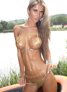 Busty chick Nessa Devil wears golden micro bikini at the river