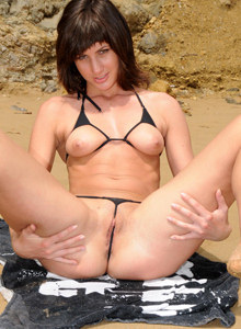 Exciting young beauty Kitty in black micro bikini with thong cameltoe on the beach and on the rocks