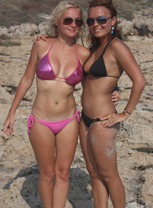 Exciting playful girls Anastasia and Regina are in shiny pink and black bikinis at the sea