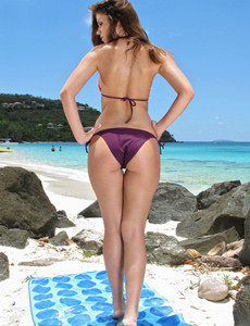 Peaches girl is on the beach wearing purple bikini and nude