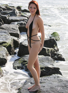 Exciting brunette Annabelle in black g-string micro bikini is swimming nude in the sea